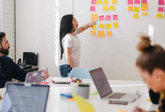 woman moving sticky notes on a board during a workshop